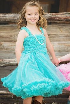 We just love this aqua blue petti dress for toddler and little girls! Do you have a little girl that loves ruffles, frills and swishy skirts? Take a gander at this sweet dress in the color fit for a princess. Made of a crisp blue fabric with a tiered tutu skirt this fun girls dress is great for spring photos, as a girls Easter outfit or for all kinds of dress up fun.