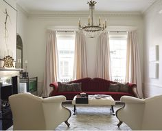 Love the big red/rust sofa with the all white decor. Designer Katie Scott