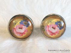 Diese wunderschönen Ohrstecker zeigen frühlingshafte rosa und blaue Blumen auf einem warmen, gelben Hintergrund.   Durchmesser Cabochon inkl. Fassung: ca. 1,5 cm  Fassung:...