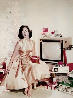 TBT to Elizabeth Taylor in this festive picture, wearing a silky, champagne-colored full dress and classic red lip