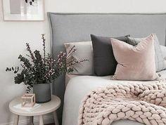 chambre rose et gris, mur couleur blanche, lit gris avec une tete de lit grise, plaid rose, coussins rose, gris et noirs, table de chevet blanche, deco florale