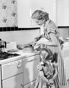 A vintage mother and daughter frosting a yummy looking cake together in the kitchen. #vintage #homemaker #family