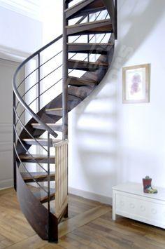 S10 - Gamme Initiale - SPIR'DÉCO® Contemporain d'Escaliers Décors®. Escalier standard d'intérieur hélicoïdal au design contemporain en acier et bois. Marches + bois. Option limon en tôle roulée soulignant les courbes du colimaçon. Rampe contemporaine. Mode d'assemblage par soudage. Finition : acier brut oxydé + vernis. - © Photo : Vanessa DESCHUYTENEER