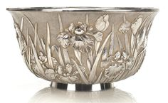 A deep silver punch bowl By Toshinaga, 20th century Double-walled with an everted mouth and set on a slightly splayed ring foot, decorated with irises hammered up in bold relief and highlighted with nanako background, signed Toshinaga koku and sealed