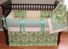 Ellie Baby Bedding  This is a truly modern custom 3 pc baby crib bedding set and includes the bumper pad, crib skirt, and blanket.  The teal/blue mod link print,  designer mod trees, ecru twill, green grosgrain ties, and ultra soft ecru minky combine softness and texture. The best for your little angel's nursery.