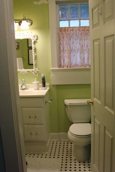 Green bathroom, white mirror, b&w checkered floor - so adorable.
