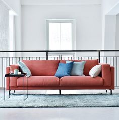 coral red linen sofa | industrial style open plan loft with huge windows | IKEA Nockeby sofa with a Bemz cover in Coral Brera Lino by Designers guild | Blue Bemz linen cushion covers