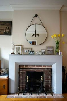 A Round Mirror Hangs From Leather Strap Above Modern Fireplace Mantel