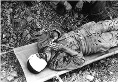 A bandaged American soldier lies on a stretcher with his hands clasped in prayer, during the fight to take Okinawa in 1945.
