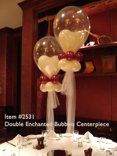 Item #2351 DOUBLE ENCHANTED BUBBLE CENTERPIECE: Large clear balloon with a smaller heart shaped white balloon inside it and capped with two rows of smaller balloon wreaths and anchored to the table with tulle ribbons surrounding a small bowl.
