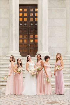 bride poes with five bridesmaids in pink dresses at Princeton University | Rainy wedding day at Chauncey Hotel with portraits at Princeton University photographed by NJ wedding photographer Idalia Photography. Find inspiration for summer wedding days here! #IdaliaPhotography #PrincetonUniversityWedding #ChaunceyHotelWedding