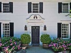 Understated and lovely entrance, capped by a terrific scrolled urn pediment, to a c1924 greystone colonial in tony Old Westbury, NY on the North Shore of Long Island. Black door, shutters, and lanterns add panache and don't miss the lintels above the first floor windows.
