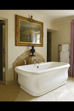A watercolor by Lady Diana Beauclerk hangs above a porcelain tub in a bathroom by Nicky Haslam