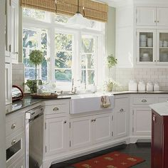An apron-front centered by a large window offers a view-filled vantage point and work space. The sink, countertop, and window combo are the visual anchor in the large white kitchen.