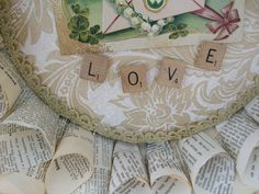 Valentine's Day love vintage book page wreath  showing close-up of vintage scrabble pieces spelling out love and an early 1900's Valentine Post Card.