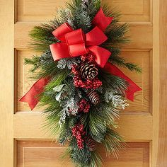 Studded with red berries and topped with a big red bow, this swag is sure to become a much-loved Christmas classic. For fullness, a long-needle teardrop-shape base anchors the holiday door arrangement.