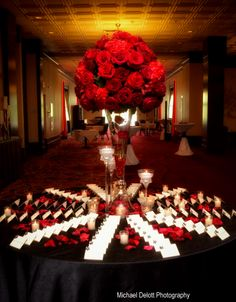 A very rich red floral centerpiece atop a tulip vase serves as place card table decor with scattered pedals and romantic candle light