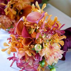 Brides: Fall Wedding Flower Ideas. Texture is the message of these elegant bridesmaids' bouquets of orchids, hybrid calla lilies and dahlias. The burgundy satin ribbon on the spines of the bouquets provides contrast to the flowers' vivid hues, Natalie Bowen Designs.