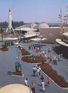 Disneyland, Tomorrowland guests stide past the Avenue of Flags toward Rocket to the Moon, 1956.