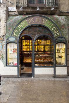 La Fábrica de Pastas Alimenticias Figueras, nacida en 1820, fue remodelada a principios del siglo XX en el estilo imperante de la época, el Modernismo Catalán. Y así, con su fachada hecha en teselas y curvas brilla desde entonces en Las Ramblas. Y aunque los dueños de la Antigua Casa Figueras ya no sea la familia Figueras, sino la pastelería Escribà, la fachada ha permanecido con los rótulos originales, pues con buen criterio creyeron que éstos, formaban parte de la historia de Barcelona.