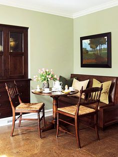 green walls with leather bench and 2 chairs
