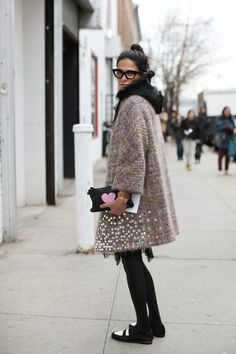 "A cold-weather outfit full of texture and whimsy, from the voluminous sequined coat layered over a hooded jacket to a clutch emblazoned with a giant heart. I also love her two-tone loafers. | ""On the Street…..21st Street, New York"", Photography by Scott Schuman / The Sartorialist #streetstyle"