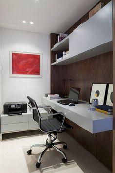Escritorio de madera lacada blanca empotrado a la pared de madera; más alto una repisa del mismo material con libros. Sobre el escritorio una laptop, libros una lámpara led de escritorio y un par de ilustraciones enmarcadas apoyadas en la pared.