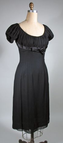 This mid 1950s silk chiffon party dress has the Empire waist with fitted torso of 1955 - 1956. The scoop neck bodice with short sleeves is covered with ruched chiffon and the empire waist it accented with a silk satin band and bow. The skirt is cut with princess seams in the front and back. There are additional godets type panels set in at the back waist that add flare to the back of the skirt. The dress is lined in black silk with a CB metal zipper to close.