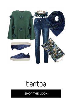 Pantaloni di jeans scuri con maglia a punto inglese con pom-pom. in linea con la tendenza di questo autunno-inverno le sneakers in ciniglia blu. sciarpa, bracciale e borsa a fantasie diverse ma unite dalle crome del verde