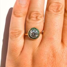 An exceptional French 1930s Trabert & Hoeffer Mauboussin engagement ring. The ring features a central 1.70ct old European cut diamond contrasted by mid-dark green emeralds surrounding the diamond set in platinum and 18ct yellow gold. The inner band is stamped THM with French control marks on the outer band.