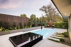 The glass like appearance of the jacuzzi is all thanks to the black mosaic tiles. These black tiles also offset the white and light blue of the pool, as well as the alpine white concrete slab surrounding the end of the pool, providing a raised platform.
