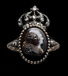 Gold and silver ring, the hoop dividing at the diamond set shoulders to support the oval bezel with beaded border enclosing a sardonyx double portrait cameo of Louis XVI and Queen Marie Antoinette, facing in profile towards the right, surmounted by the diamond set royal crown of France. At the back there is a silver wire monogram of the initials LM. With stamped leather ring box. French, c. 1774.