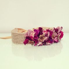 Diseño de cinturón con cuerda de pasamanería dorada metalizada y adorno de flores en tonos magenta y fucsias.   Disponibles en una amplia ga...