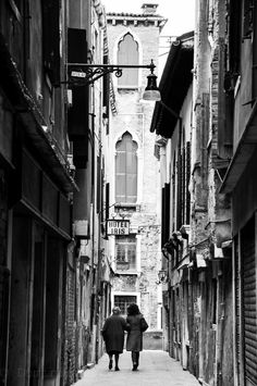 B, old couple walking the streets of Venice, Italy.