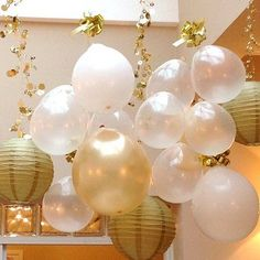 New Year's Balloon Decorations - White, clear, and golden balloons -- along with inexpensive paper lanterns -- cascade from the ceiling, held aloft by golden garlands and bows.