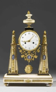 Ormolu & White Marble PORTICO CLOCK - Movement flanked by two obelisks. The upper part decorated with a vase. Medallions in imitation of Wedgwood Porcelein. White enamel dial. End of the eighteenth century.