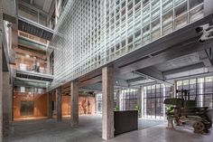 Exposed concrete structures and narrow-framed steel windows were retained to evoke the buildings' industrial heritage. The architects also sought to enhance the connection between the former production spaces and the surrounding plantation. Chinese Courtyard, Structure And Function, Steel Windows, Exposed Concrete, Concrete Structure, Factory Design, Industrial Interiors, Ground Floor Plan, Courtyard House