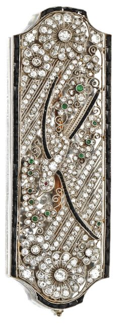 An Art Deco diamond, onyx and emerald brooch, French, circa 1925. The openwork plaque depicting a bird in flight within a floral border, set with numerous old European-cut, single-cut and rose-cut diamonds, further decorated with calibré-cut onyx, small round emeralds and a square-cut ruby, mounted in platinum, maker's mark, assay mark. #ArtDeco #brooch