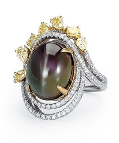 This phenomenal 14.88 carat cat's eye Alexandrite set in a basket of yellow gold is encircled by a setting of white gold and white diamonds finished with an exquisite crown of fancy colored yellow diamonds. Diamond Info: 07-YD 1.19, 94-RD 0.45, 01-ALX 14.88 CTS Fits center stone size OV: 15x13 MM GUIDE Price may vary depending on center stone.