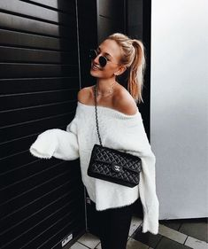 Cozy white off the shoulder sweater with black handbag and jeans.