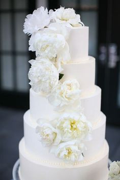 Six-tiered white wedding cake adorned with a cascade of peonies | Photo by Lane Dittoe