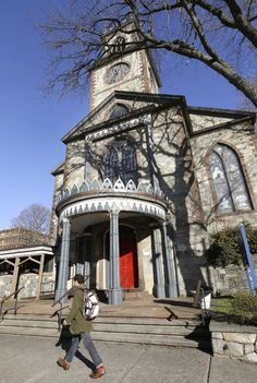 In this Wednesday, Nov. 19, 2014 photo, a pedestrian walks past an entrance to the Cathedral of St. John of St. John Episcopal Church, in Providence, R.I. The Episcopal Diocese of Rhode Island has approved a plan to open in the shuttered church what would be the nation's first museum devoted to examining the history and church's role in the sometimes-buried legacy of slavery in northern states like Rhode Island. (AP Photo/Steven Senne)