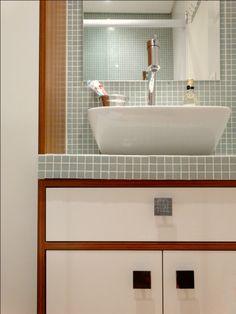 Neste banheiro, o arquiteto Glaucio Gonçalves projetou uma bancada revestida com pastilhas. Veja o antes e depois da reforma feita pelo arquiteto nesse apartamento de apenas 23 m², no qual o objetivo era aproveitar bem todos os espaços: http://www.webcasas.com.br/revista/materia/decoracao/405/confira-antes-e-depois-de-ape-de-23-m/