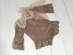 An elegant romper in a beautiful chocolate brown knit. Vintage lace makes up the smart collar and a chiffon bow adorns one shoulder. Ties at the back for a perfect fit.Please note: lace collars are all slightly different.