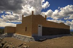A tire-bale wall surrounds this spacious passive solar home under construction. Fremont County, CO.