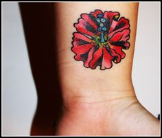 A bold pop of color in a floral wrist tattoo makes a gorgeous permanent decoration.