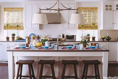 """In a Newport summer house, architect Steven Laurin designed the kitchen island, reminiscent of a farm table except for its top of Caesarstone, a quartz composite from CaesarStone USA. Designer Meg Braff chose the Sloan Street Shop Light, a large double pendant fixture from Visual Comfort, to balance out the large island and warm up the room: """"It's more atmospheric than recessed lighting, and it's nice having linen shades as opposed to metal ones.""""   - HouseBeautiful.com"""