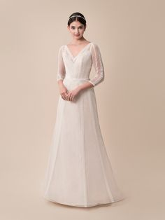 In delicate point d'esprit with soft lace trim, the 3/4 sleeve boho wedding dress Moonlight Tango style T789 boasts graceful charm and timeless allure in an incredibly romantic silhouette. This A-line wedding gown has an understated look with 3/4 length sleeves, a V-neckline, a low V-back, and artfully placed lace details that highlight the bust and hips in the most feminine way. Trimmed with a row of covered buttons that trail along the zipper and a sweeping train for added beauty,...