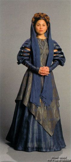 Revenge of the Sith: Queen of Alderaan and wife of Bail Organa, Breha Organa wears a beautiful blue brocade gown with slit sleeves when she first meets her newly adopted daughter. Her outfit is completed by a shawl that reaches her knees and a traditional, braided Alderaanian hairstyle.