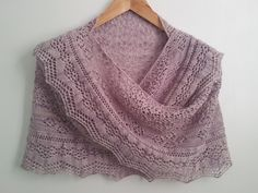 This crescent shaped shawl is knitted in one piece from the centre top down and has a knitted on border. The main body of the shawl uses a rosebud mesh, while there are more bunches of roses on the outer edge and a string of roses in the border lace. Astrid 'helped' a lot, so this shawl is named for her.